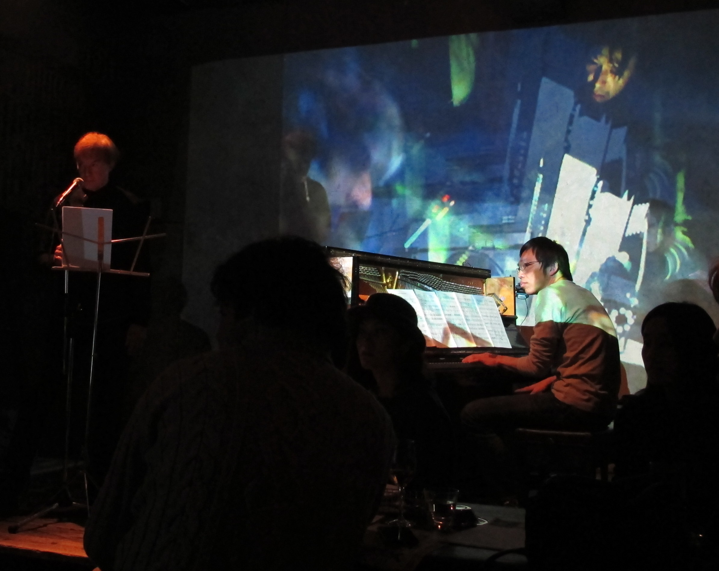 At an Ensō Watt performance there are two screens, one poet, and musicians positioned around the room... The audience is bathed in light and sound.