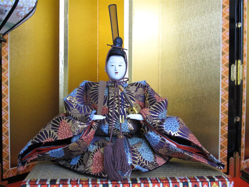The Emperor bears a ritual baton (笏 shaku) representing his authority.