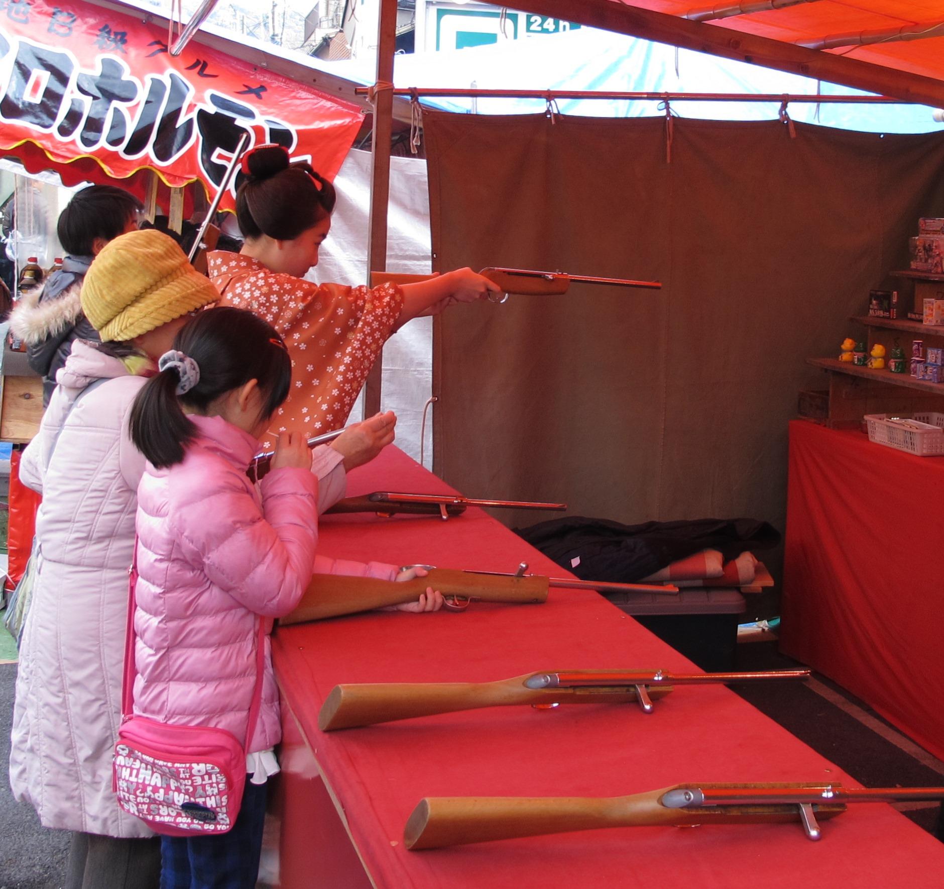A shooting range among the stalls. Can you see the maiko?